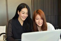 Femmes asiatiques d'affaires à l'aide de l'ordinateur dans le bureau Images stock