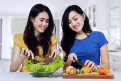 Femmes asiatiques faisant cuire la salade dans la cuisine Photographie stock