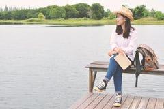 Femmes asiatiques heureuses lisant un livre et un sac à dos Photo libre de droits