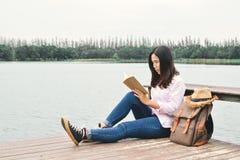 Femmes asiatiques heureuses lisant un livre et un sac à dos Photos libres de droits