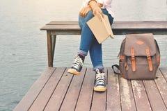 Femmes asiatiques heureuses lisant un livre et un sac à dos Photographie stock