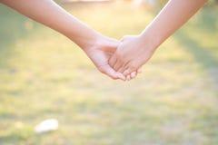 Femmes asiatiques se serrant la main dans la chaleur de la lumière de matin Photographie stock