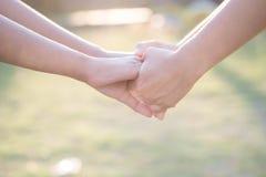 Femmes asiatiques se serrant la main dans la chaleur de la lumière de matin Photos stock
