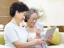 Femmes asiatiques supérieures à l'aide de la tablette Image stock