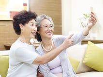 Femmes asiatiques supérieures prenant un selfie Images stock