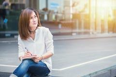 Femmes asiatiques woking à la main extérieure avec la note d'écriture de stylo Photo stock