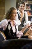 Femmes assez jeunes s'asseyant sur le fauteuil dans la bibliothèque Photographie stock