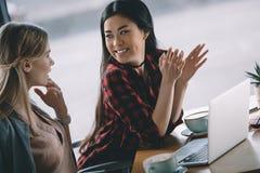 Femmes attirantes sur la pause-café avec l'ordinateur portable en café Photographie stock libre de droits