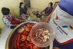 FEMMES AU FOYER FAISANT CUIRE ENSEMBLE Photos stock