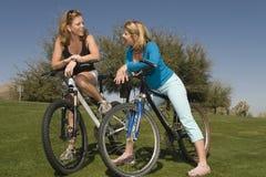 Femmes avec des bicyclettes communiquant en parc Photo stock