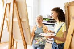 Femmes avec des chevalets et des palettes à l'école d'art Image stock