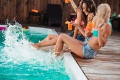 Femmes avec des cocktails riant et ayant l'amusement près de la piscine Photo stock