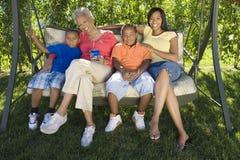 Femmes avec des enfants sur l'oscillation Image stock
