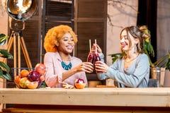 Femmes avec des fruits et des smoothies à la maison Photographie stock