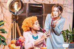 Femmes avec des fruits et des smoothies à la maison Photo stock