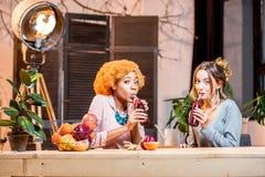 Femmes avec des fruits et des smoothies à la maison Image libre de droits