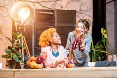 Femmes avec des fruits et des smoothies à la maison Photographie stock libre de droits