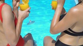 Femmes avec des jambes en cocktails tintants et potables de piscine, loisirs d'été banque de vidéos