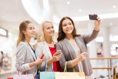 Femmes avec des smartphones faisant des emplettes et prenant le selfie Photos stock