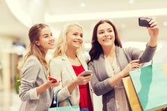 Femmes avec des smartphones faisant des emplettes et prenant le selfie Images stock