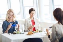Femmes avec des smartphones prenant la photo de la nourriture Photographie stock libre de droits