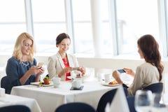 Femmes avec des smartphones prenant la photo de la nourriture Photographie stock