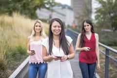 Femmes avec du charme avec le téléphone portable dehors dans la ville Images stock