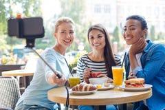 Femmes avec du charme prenant des selfies avec le monopod en café Images stock