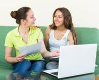 Femmes avec l'ordinateur portable dans l'intérieur à la maison Photo stock