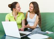 Femmes avec l'ordinateur portable dans l'intérieur à la maison Photographie stock libre de droits