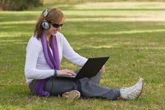 Femmes avec l'ordinateur portatif et les écouteurs Photographie stock libre de droits