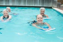 Femmes avec la natation de kickboard dans la piscine Image libre de droits