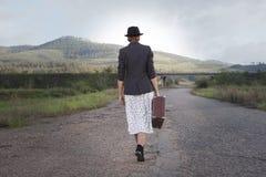 Femmes avec la valise de vintage à la vieille route Photos stock