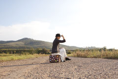 Femmes avec la valise de vintage à la vieille route Photographie stock
