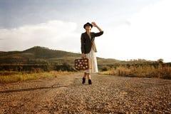 Femmes avec la valise de vintage à la vieille route Photo dans le rétro type Photo libre de droits