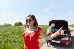 Femmes avec la voiture cassée faisant de l'auto-stop à la campagne Images libres de droits