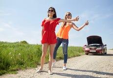 Femmes avec la voiture cassée faisant de l'auto-stop à la campagne Photos stock