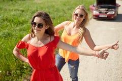 Femmes avec la voiture cassée faisant de l'auto-stop à la campagne Photographie stock