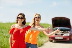 Femmes avec la voiture cassée faisant de l'auto-stop à la campagne Photo stock