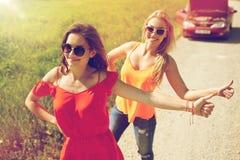 Femmes avec la voiture cassée faisant de l'auto-stop à la campagne Images stock