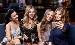 Femmes avec le champagne prenant le selfie à la boîte de nuit Images stock
