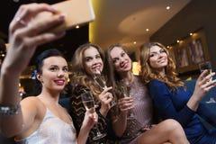 Femmes avec le champagne prenant le selfie à la boîte de nuit Photo libre de droits