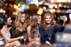 Femmes avec le champagne prenant le selfie à la boîte de nuit Images libres de droits