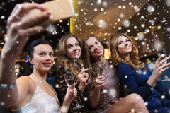 Femmes avec le champagne prenant le selfie à la boîte de nuit Image stock