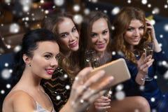 Femmes avec le champagne prenant le selfie à la boîte de nuit Photo stock