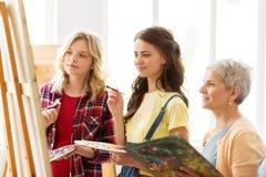 Femmes avec le chevalet et les palettes à l'école d'art Image stock