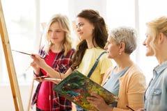 Femmes avec le chevalet et les palettes à l'école d'art Photos stock