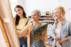Femmes avec le chevalet et les palettes à l'école d'art Images libres de droits