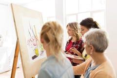 Femmes avec le chevalet et les palettes à l'école d'art Photo stock