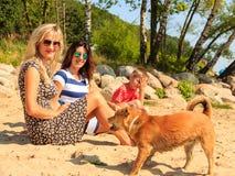 Femmes avec le chien et l'enfant détendant sur la plage Photo stock